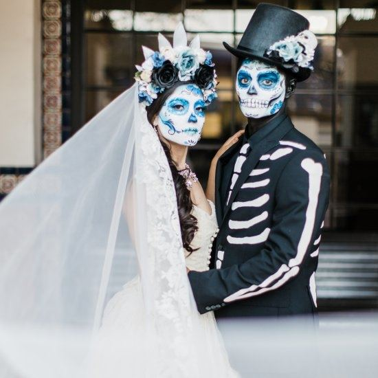 Couple dressed as bride and groom wearing face paint for Dia de Los Muertos/Day of the Dead celebration