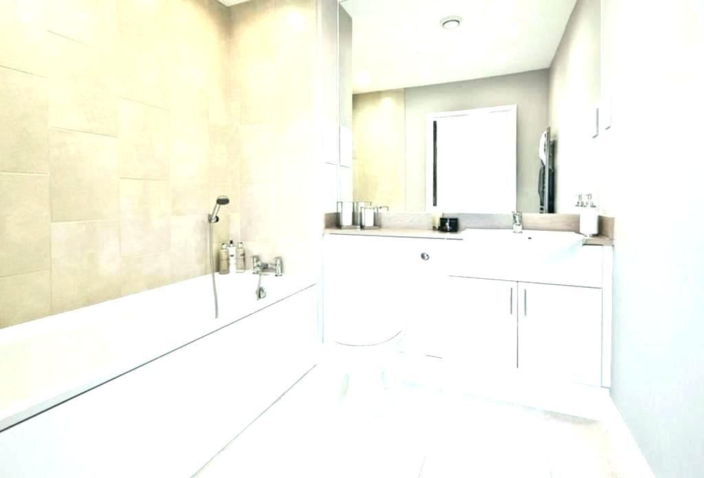 Beige tile bathtub surround with oil rubbed bronze fixtures