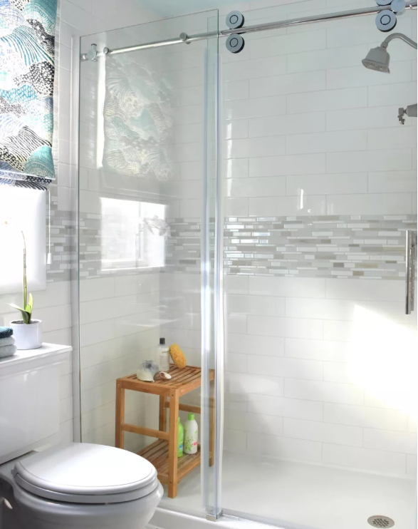 The deluxe bathroom has a deep soaking tub and vertically positioned subway  tiles