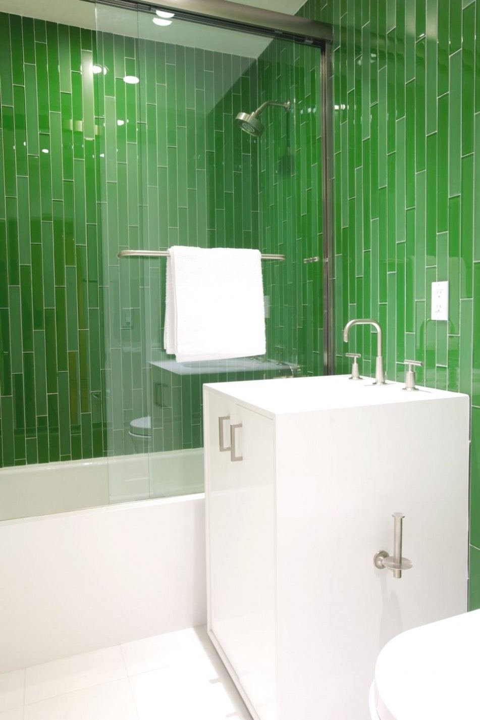 Long, thin green tiles in a vertical pattern around a white bathtub and vanity