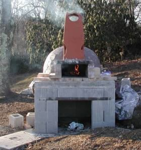 The oven is being handcrafted, stone by stone, with tremendous skill and  artistry